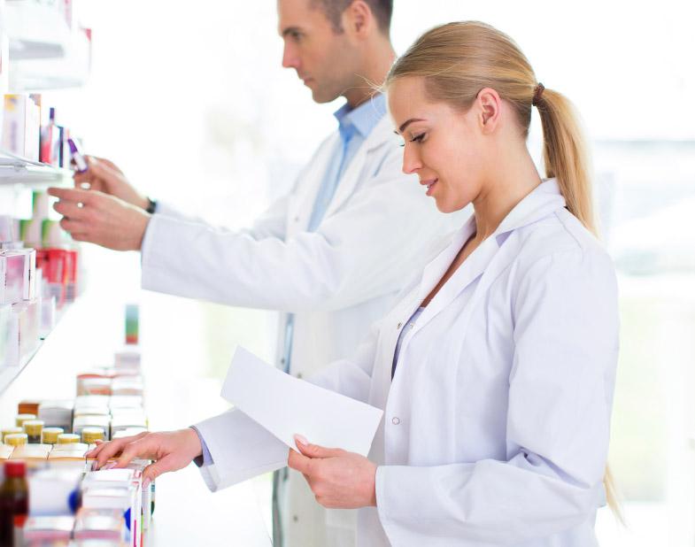 farmaceuci w fartuchach przeglądają leki